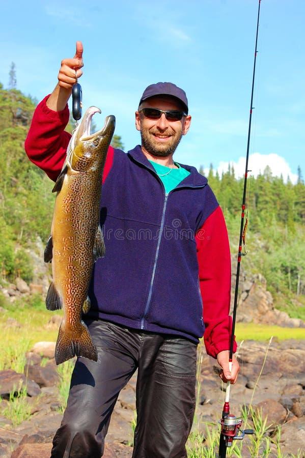 Fiskaren väger en härlig manlig lax royaltyfri fotografi