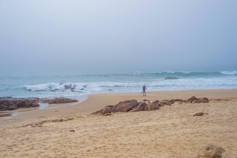 Fiskarepersonsihouette med metspöet på den tomma stranden arkivfoto