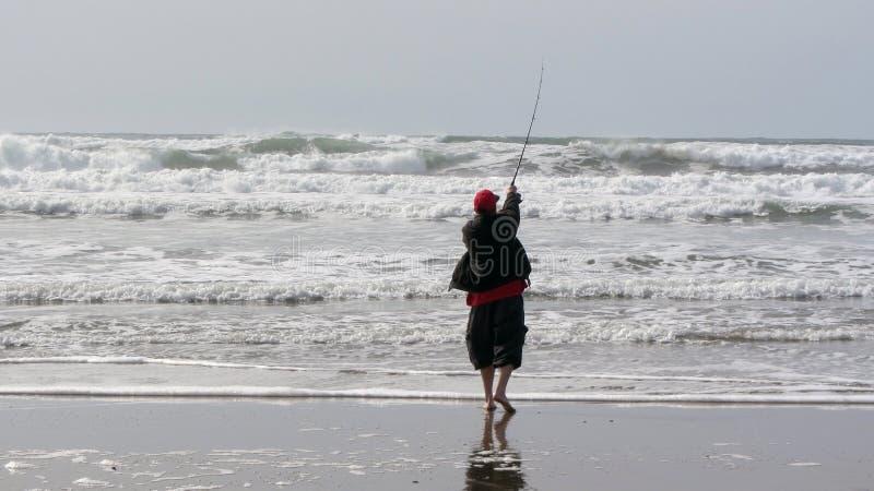 Fiskarerollbesättning in i bränning fotografering för bildbyråer