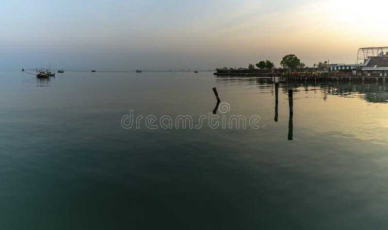 Fiskares hus och sj?sidahus i Sattahip som reflekterar med vattenyttersidan ljus sky royaltyfri foto