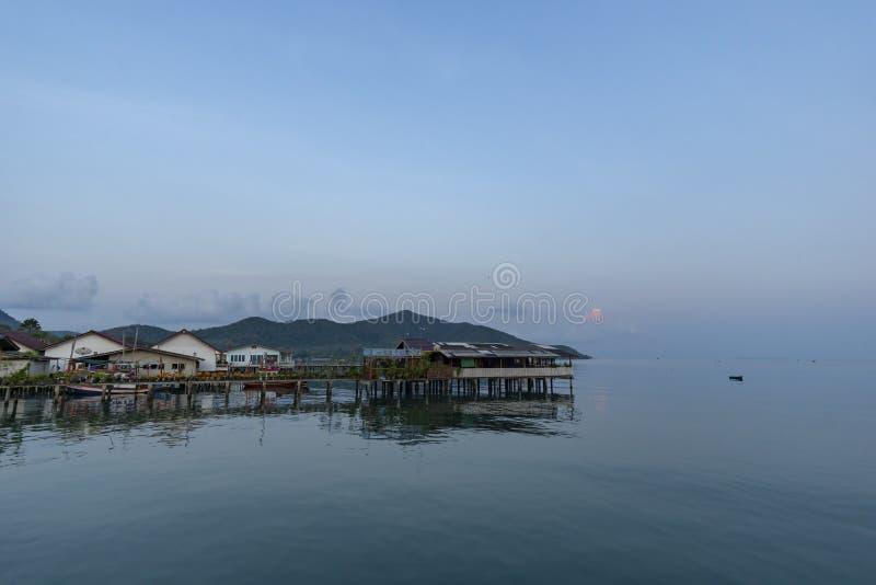 Fiskares hus och sj?sidahus i Sattahip som reflekterar med vattenyttersidan ljus sky fotografering för bildbyråer