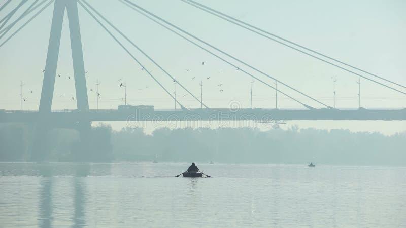 Fiskaresegling under den stora bron på det uppblåsbara fartyget, dimmigt väder, storstad arkivfoton