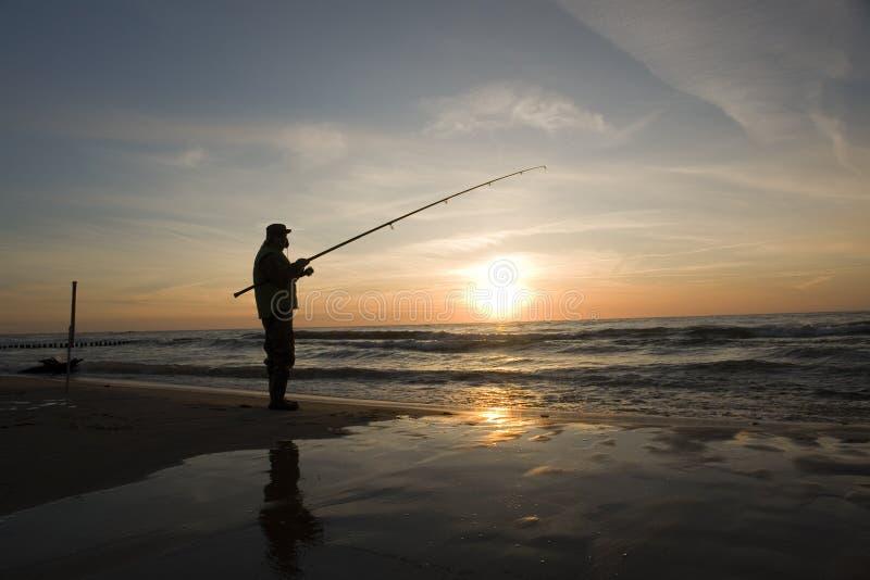fiskaresilhouettesolnedgång arkivfoton