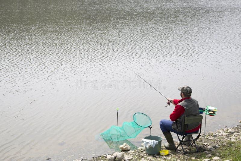 FiskareSitting In The stol på den Reeling rad- och kastaRod Into The River för flodstrand royaltyfri foto