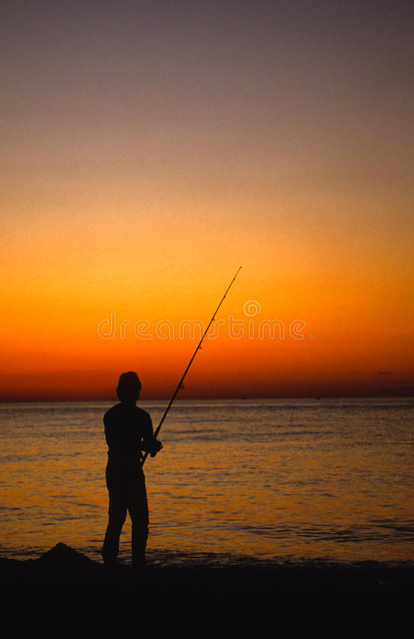 fiskaresolnedgångbränning royaltyfria foton
