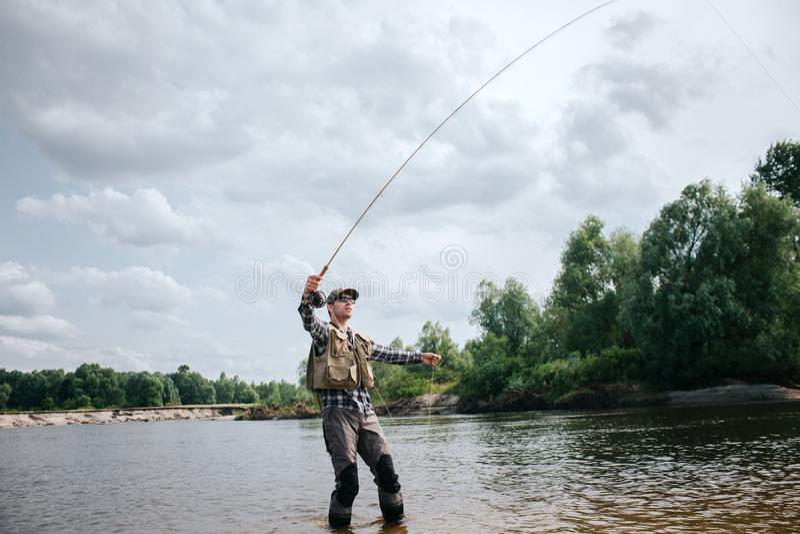 Fiskareställningar i grund och för innehav klipsk stång upp i en hand och del av skeden i annan Mannen ser upp Honom royaltyfri foto