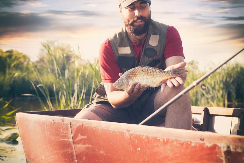 fiskarevisningfisk som ler manfiske som helghobby royaltyfri foto