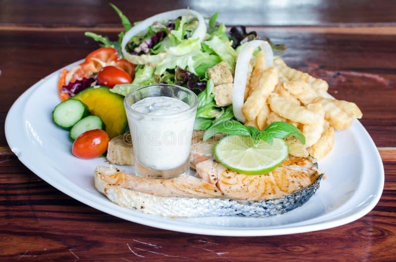 Fiskbiff, grillad lax och sallad för ny grönsak, franska fri royaltyfri bild