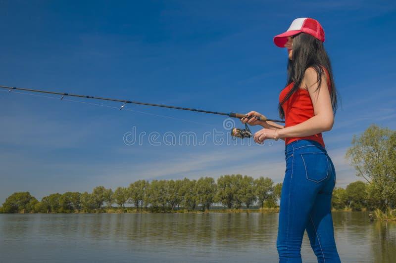 fiske Den unga sexiga kvinnan fångar fisken vid snurrstången på sjön i sommar royaltyfria foton