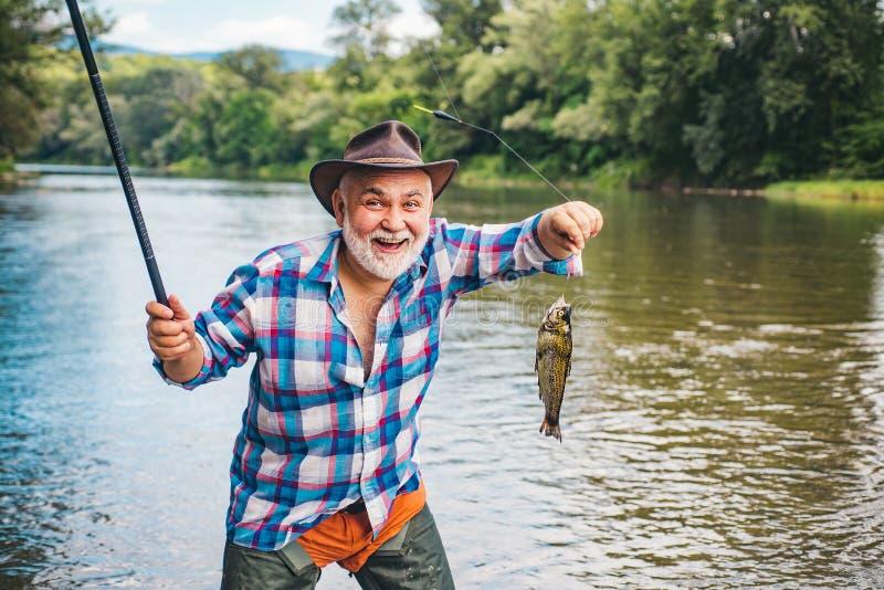 Fiske efter regnbåge Fiske efter krokar Fiskare och troféöring Regnbåge på krok Fiske blev en royaltyfri foto