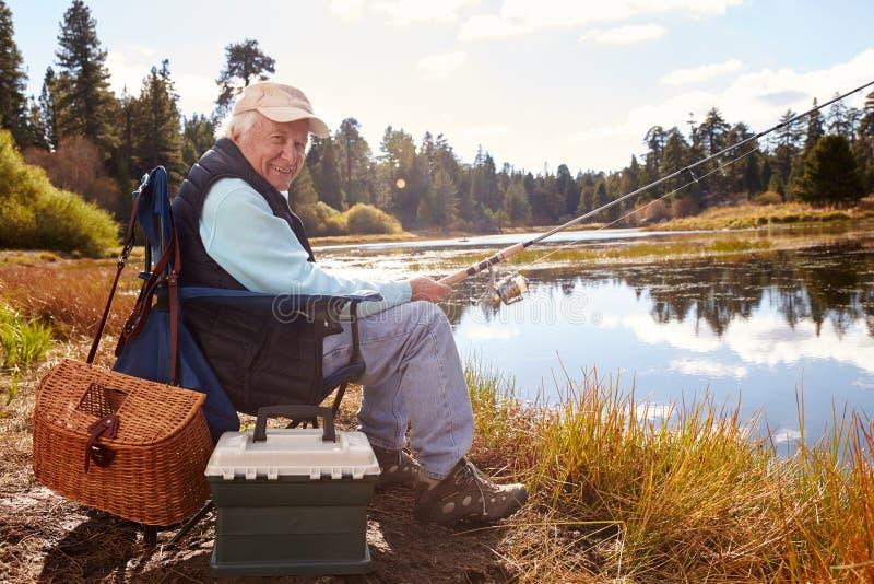 Fiske för hög man i en sjö som ser till kameran, Kalifornien royaltyfria foton