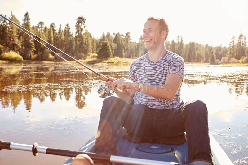 Fiske för ung man från kajaken på sjön royaltyfri bild