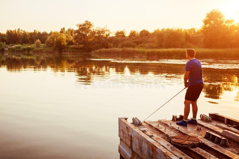 Fiske för ung man på flodanseende på bron på solnedgången Lycklig fiserman som tycker om hobby royaltyfri foto