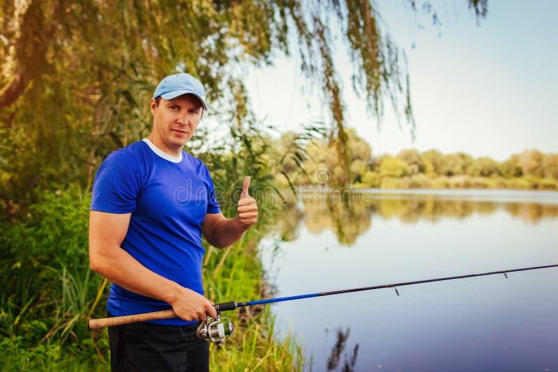 Fiske för ung man på floden Lycklig fisermanvisningtumme upp Hobbybegrepp Sommaraktiviteter royaltyfri fotografi