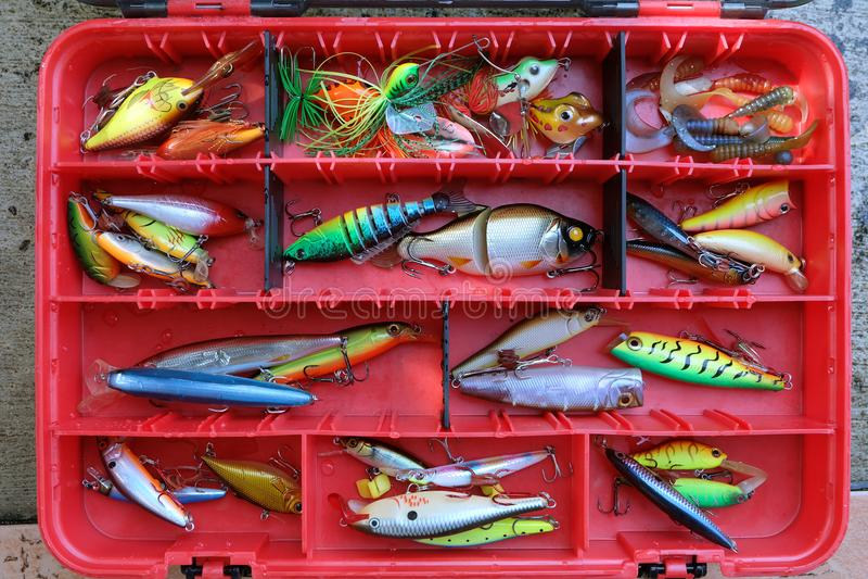 Fiske lockar i det röda askhjälpmedlet för sport arkivbilder