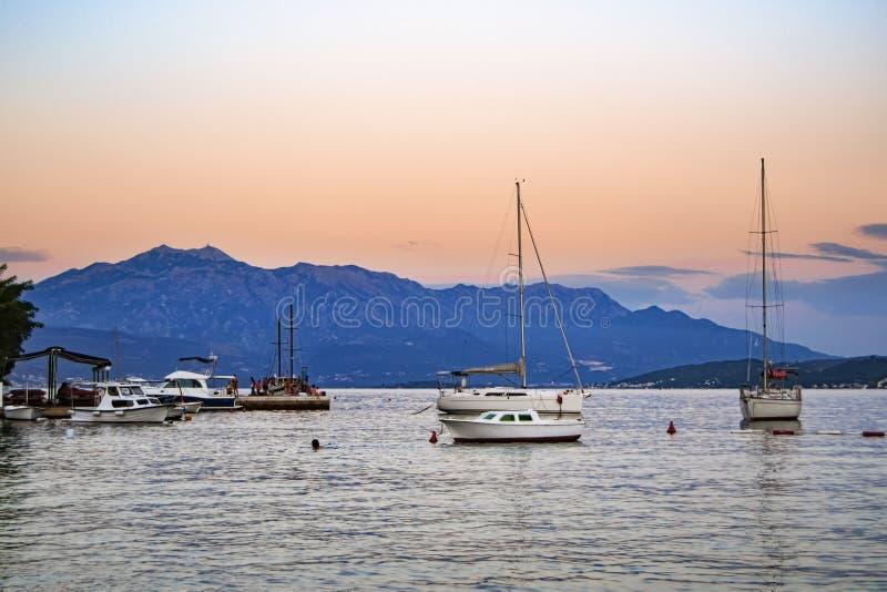 Fiske- och nöjefartyg på ankaret i en pittoresk havsfjärd på solnedgången fotografering för bildbyråer