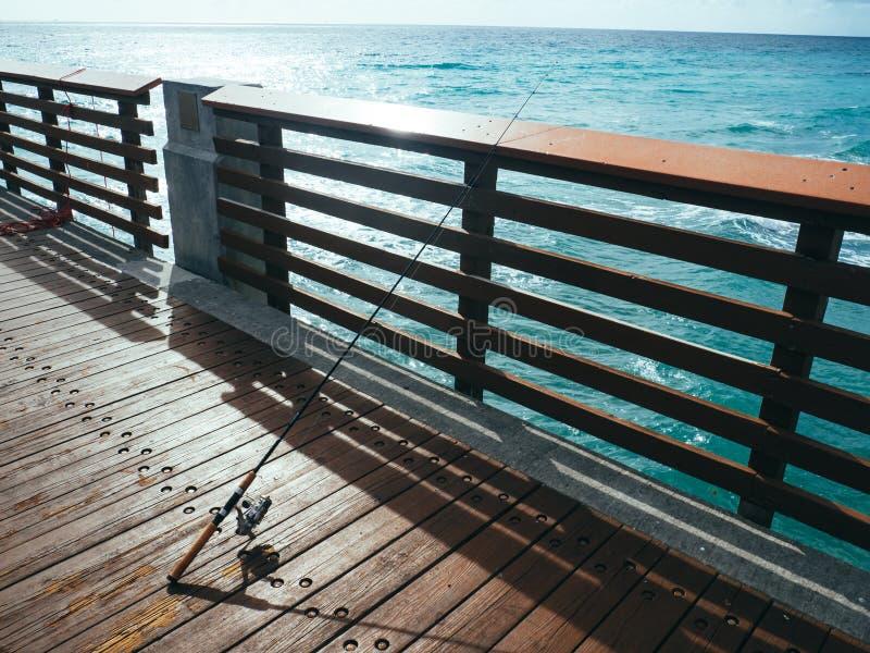 Fiske Pole på pir på havet royaltyfria bilder