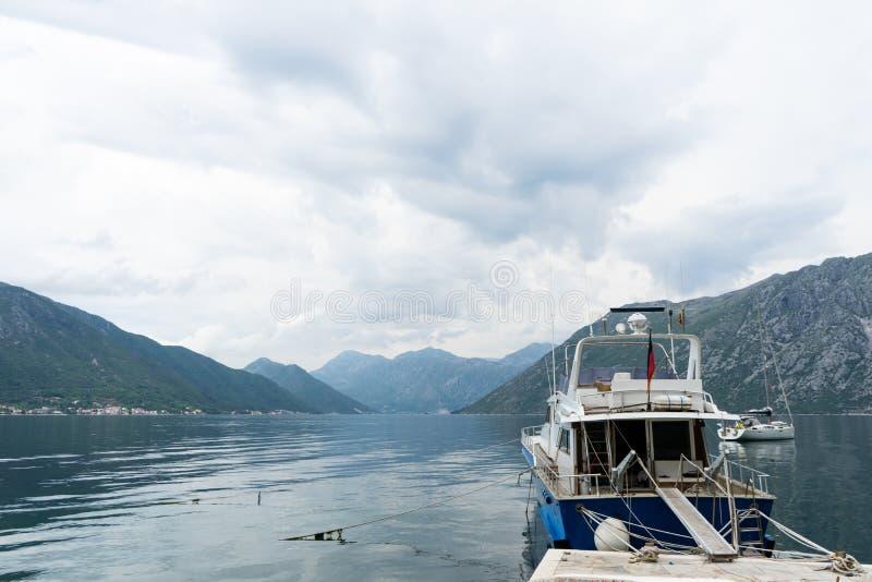 Fiskebåt i den lilla hamnen av Kotor Sjö med små yachter och kuststäder och berg i bakgrunden Pir med arkivfoton