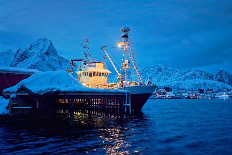 Fiskebåt i den Reine byn på natten Lofoten öar, Norge royaltyfri foto
