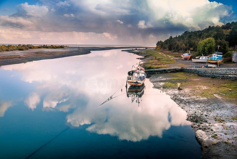 Fiskebåt i reflexionen av molnet på floden vid havet, Aytuy, Chiloe ö, Chile, Sydamerika royaltyfri fotografi