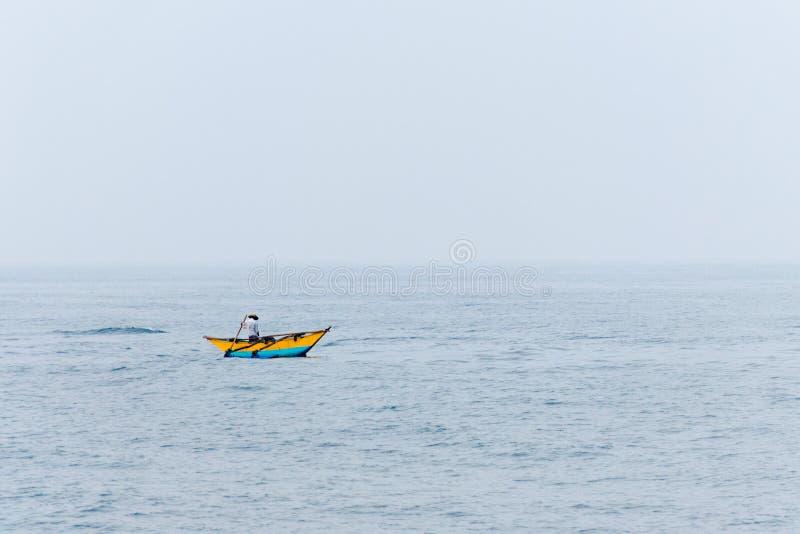 Fiskebåt i sjön på den dimmiga morgonen Liten man bland det stora ändlösa havet royaltyfria foton