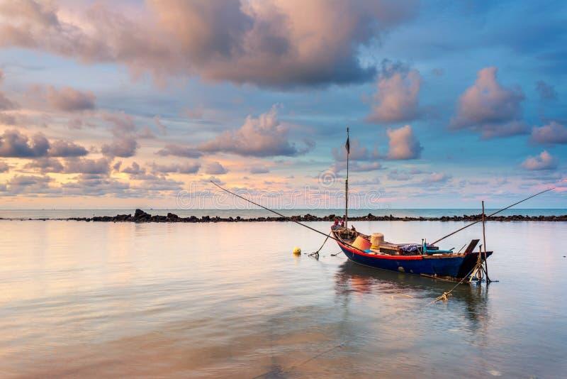 Fiskebåt i vatten för perfekt lugna hav som exponeringsglas med molnen i himlen, lång exponering som tas under soluppgång royaltyfri fotografi
