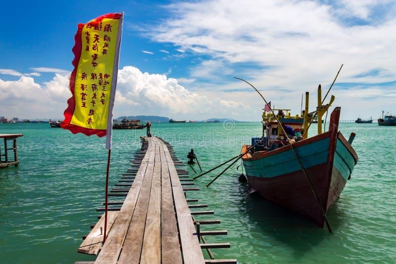 Fiskebåt med en träbro med kinesisk flagg i Tan Jetty, Clan Jetties, Georgetown, Penang, Malaysia arkivfoto