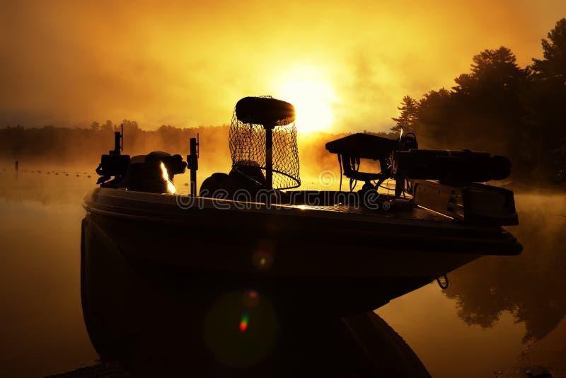 Fiskebåt med gryningfiskeutrustning i dimman på en skogsjö fiska i USA maine USA royaltyfri fotografi