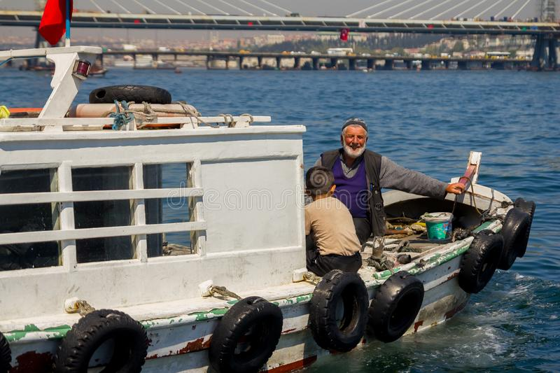 Fiskebåt på Bosporusen som omges av seagulls i Turkiet arkivbilder