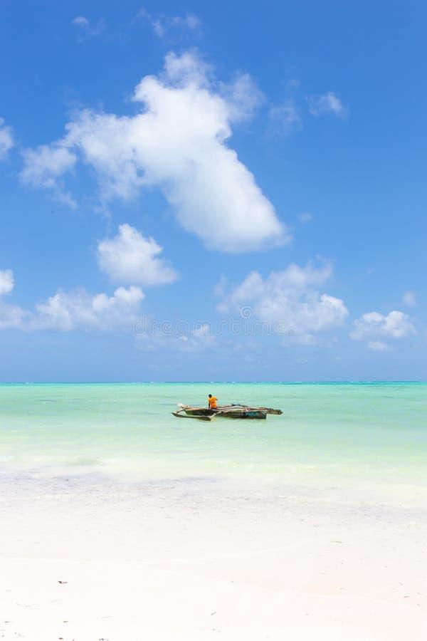 Fiskebåt på den perfekta vita sandiga stranden för bild med det turkosblåa havet, Paje, Zanzibar, Tanzania arkivfoton