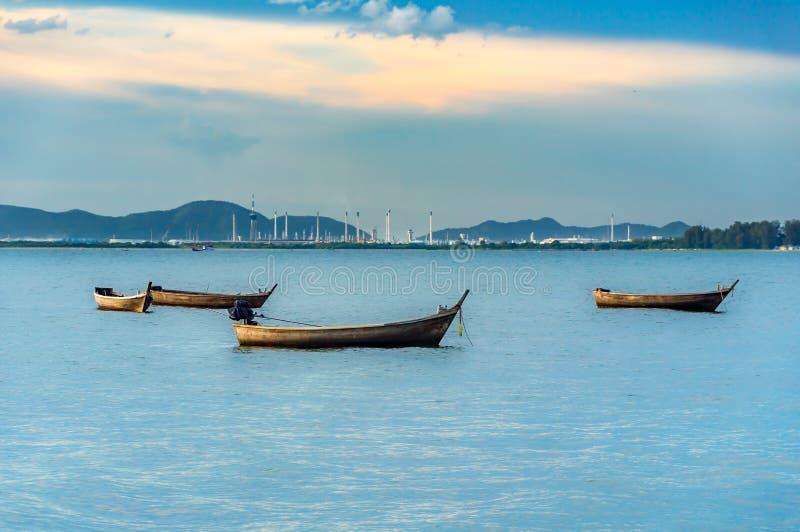 Fiskebåt på havssikten av industriell behållarelastfreig arkivfoto
