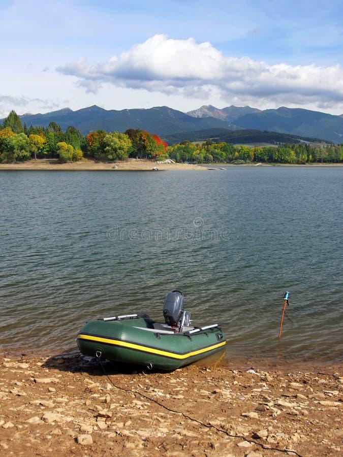 Fiskebåt på Liptovska Mara under höst royaltyfria bilder