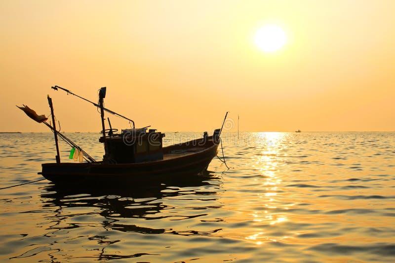 Fiskebåt på solnedgången arkivfoton