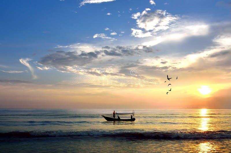 Fiskebåt på soluppgång (selektiv fokus. Fokus på fartyget endast arkivbild