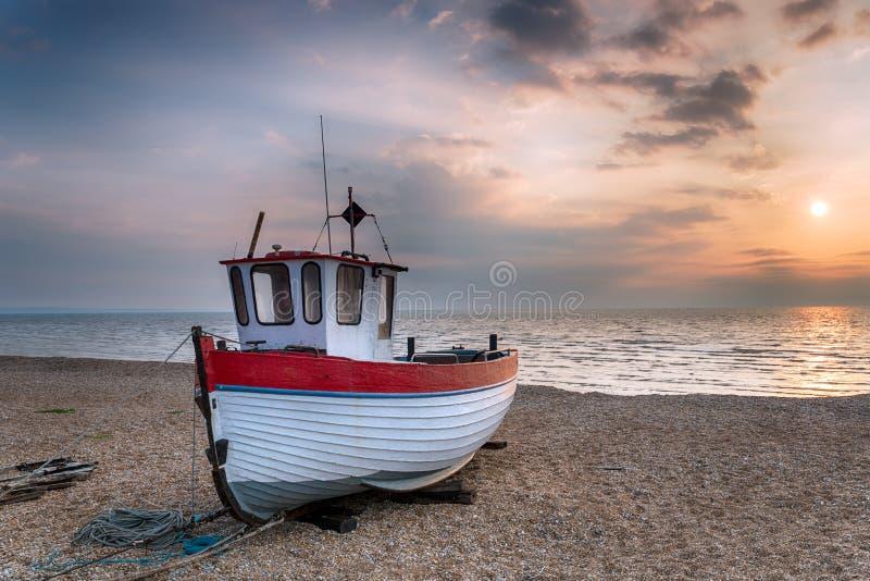 Fiskebåt på soluppgången arkivbild