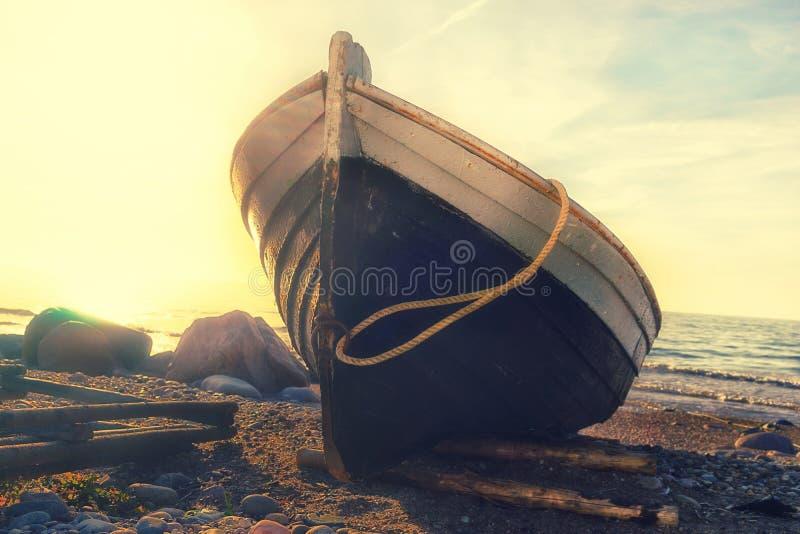 Fiskebåt på stranden på solnedgången royaltyfri fotografi