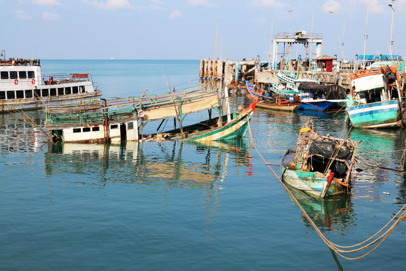 Fiskebåt som kapsejsas på pir arkivfoto