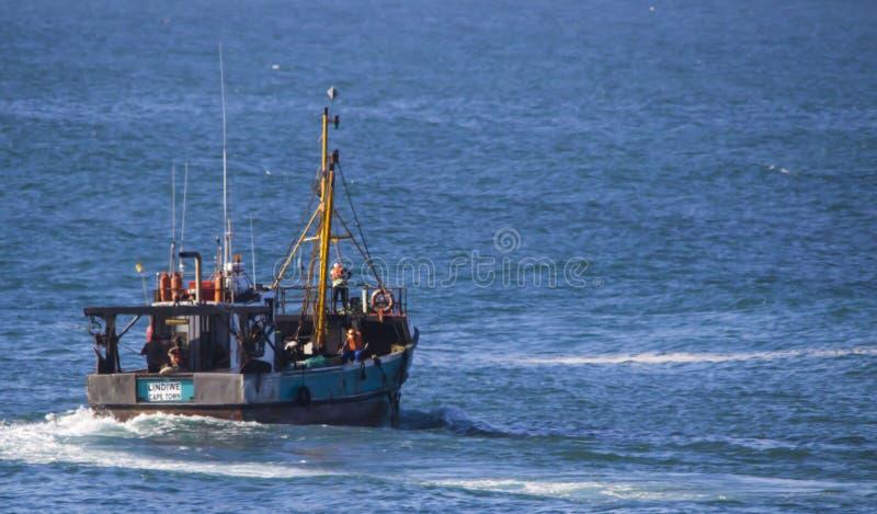 Fiskebåt som lämnar hamnen fotografering för bildbyråer