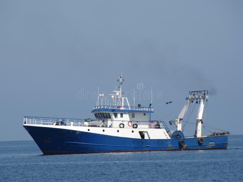 Fiskebåt som svävar på ett hav royaltyfri bild