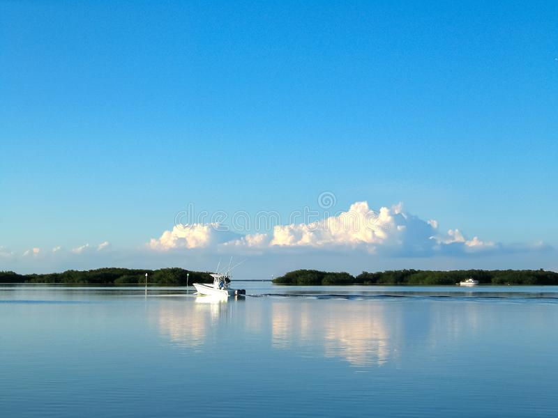 Fiskebåt ut på vattnet i Florida tangenter med land i avståndet och de enorma fluffiga molnen reflekterade i det mycket blåa have royaltyfri fotografi