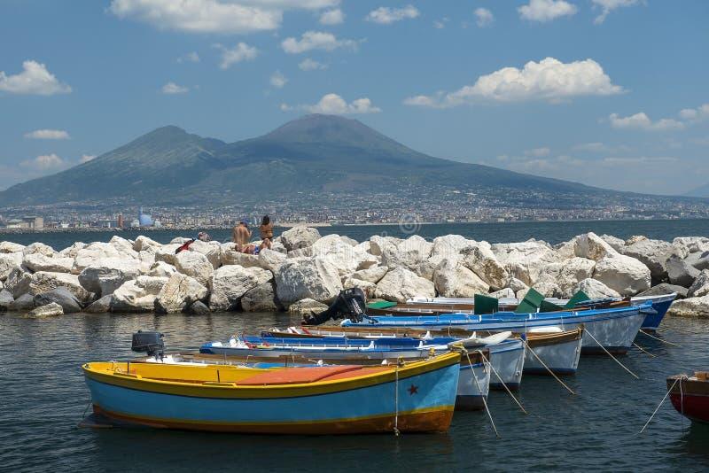 Fiskebåtar i porten av Naples och sikt av Mount Vesuvius arkivbilder
