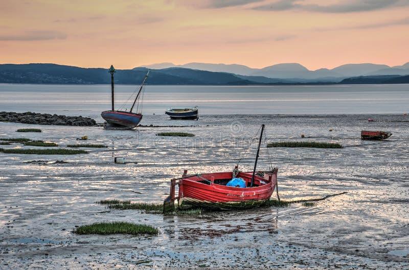 Fiskebåtar och gyttjiga landremsor på skymning arkivbild