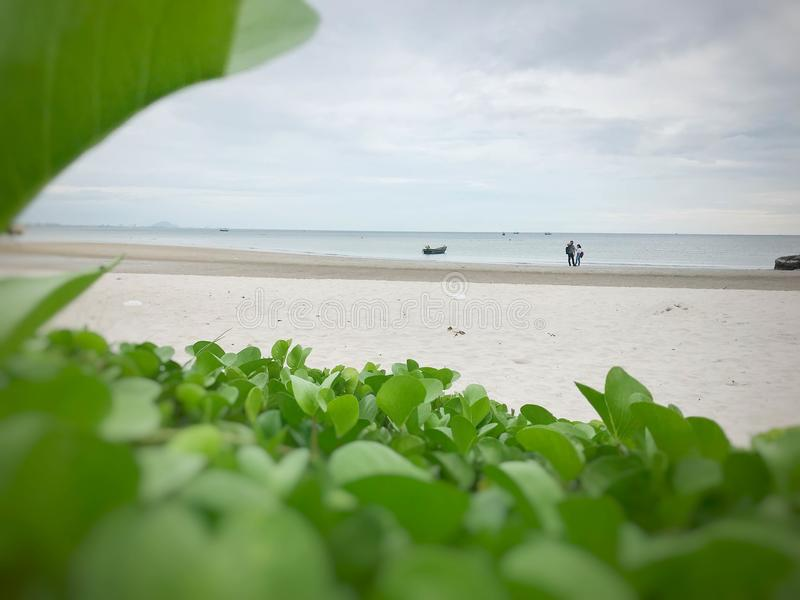 Fiskebåtar och par som är förälskade på beachfront royaltyfria bilder
