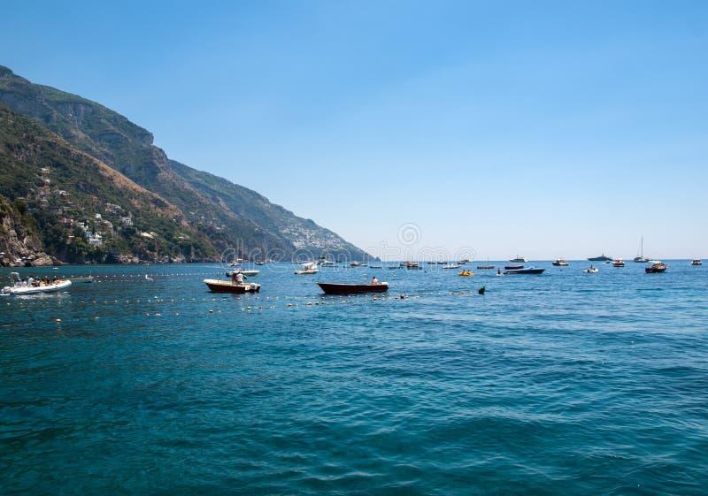 Fiskebåtar och yachter som förtöjas i det Tyrrhenian havet nära Positano, Amalfi kust Italien royaltyfri bild