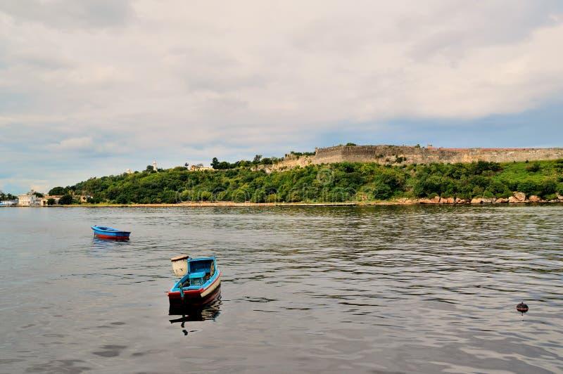 Fiskebåtar på ankringen nära den Malecon stranden, sikt av havskanalen, väggar av fästningen av San Carlos de la Cabania arkivfoton