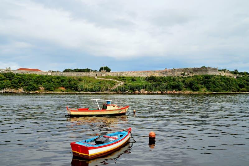 Fiskebåtar på ankringen nära den Malecon stranden, sikt av havskanalen, väggar av fästningen av San Carlos de la CabaniaC royaltyfri foto