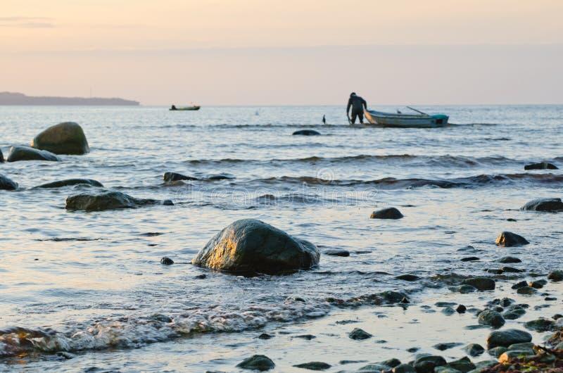 Fiskebåtar på kusten av Östersjön på solnedgången arkivbilder
