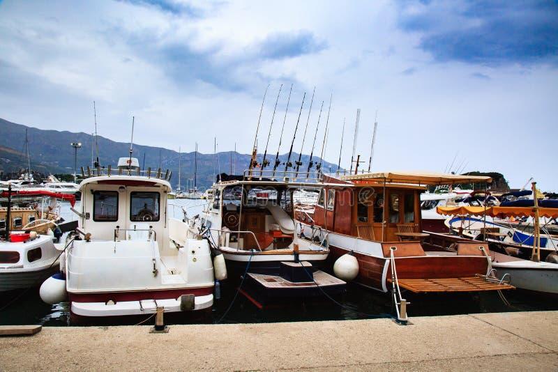 Fiskebåtar på pir i molnig dag Motoriska fartyg som anslutas i hamn royaltyfria bilder