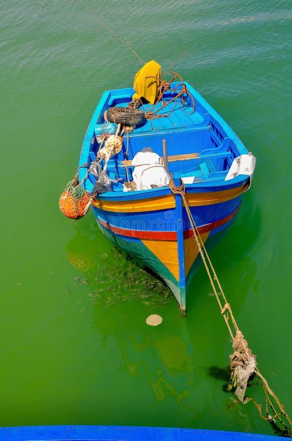 fiskebåten med fångstredskapkostnader på ett ankare i en fjärd, ett stort antal små fiskar äter upp foderrestna runt om arkivfoton