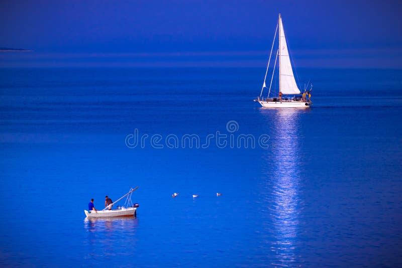 Fiskebåten och segelbåten möter i det blåa havet arkivbilder